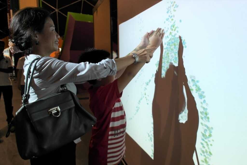 Parent guiding their child at the sand-falling interactive exhibit