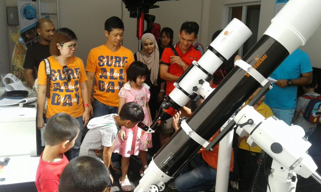 Parents and their children exploring the telescope in the PIXO observatory