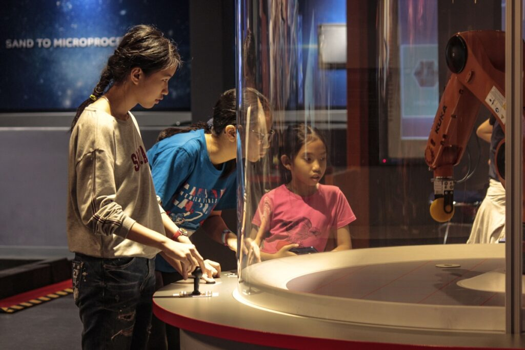 Visitors operating and observing the robot arm exhibit